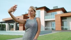 Smiling woman making selfie near apartment. Closeup blonde woman taking photo stock footage