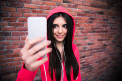 Smiling woman making selfie photo over brick wall Stock Image