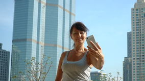 Smiling woman making selfie at the skyscraper background stock video