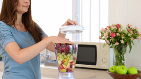 Smiling woman making a smoothie stock footage