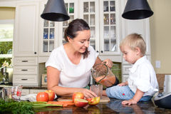 Smiling woman making smoothie for small boy Stock Photo