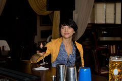 Smiling woman making a toast. Raising her glass of red wine as she sits alone at the counter in a pub or bar, with copyspace stock images