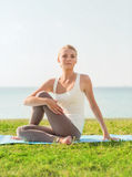 Smiling woman making yoga exercises outdoors Royalty Free Stock Photos
