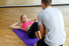 Smiling woman with male trainer exercising in gym. Sport, fitness, lifestyle and people concept - smiling women with male personal trainer exercising in gym Stock Photos