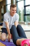 Smiling woman with male trainer exercising in gym Royalty Free Stock Images