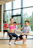 Smiling woman with male trainer exercising in gym Stock Images