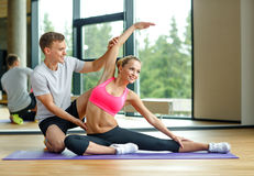 Smiling woman with male trainer exercising in gym. Sport, fitness, lifestyle and people concept - smiling women with male personal trainer exercising in gym Stock Image