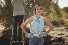 Smiling woman with man in background at olive farm Stock Photo