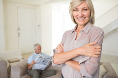 Smiling woman with man reading newspaper at home Royalty Free Stock Images