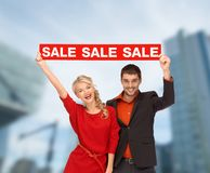 Smiling woman and man with red sale sign Stock Image
