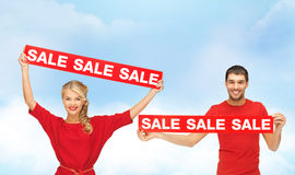 Smiling woman and man with red sale signs Stock Photo