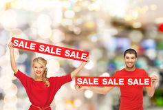 Smiling woman and man with red sale signs Royalty Free Stock Photo