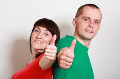 Smiling woman and man showing thumbs up Stock Photos