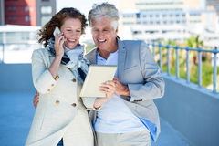 Smiling woman with man using digital tablet Royalty Free Stock Photography