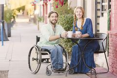 Smiling Woman with Man in Wheelchair. Woman having coffee with male friend in wheelchair Royalty Free Stock Photo