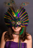 Smiling Woman in Mardi Gras Mask. A portrait of a happy young woman wearing a Mardi Gras mask, beads, and makeup Stock Photography