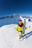 Smiling woman in mask standing and holding ski. And ski poles during sunny winter day on Krasnaya polyana ski resort and Caucasus mountains in Sochi, Russia Stock Photography