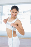 Smiling woman measuring chest in fitness studio Stock Image