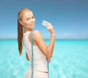 Smiling woman with measuring tape and diet pills Royalty Free Stock Photos