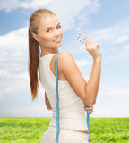 Smiling woman with measuring tape and diet pills Stock Photo