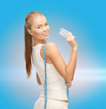 Smiling woman with measuring tape and diet pills Stock Images