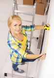 Smiling woman measuring wall Stock Photos