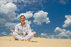 Smiling woman meditating on desert Stock Photography
