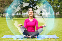 Smiling woman meditating on mat outdoors Stock Image