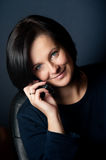 Smiling woman with mobile. Smiling young woman with mobile telephone; studio background Stock Photo