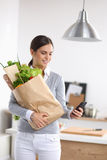 Smiling woman with mobile phone holding shopping Royalty Free Stock Images