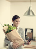 Smiling woman with mobile phone holding shopping Stock Photo