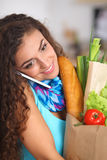 Smiling woman with mobile phone holding shopping Stock Image