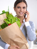 Smiling woman with mobile phone holding shopping bag in kitchen Stock Photography
