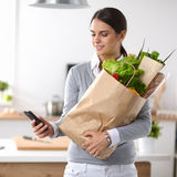 Smiling woman with mobile phone holding shopping bag in kitchen Stock Images
