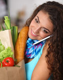 Smiling woman with mobile phone holding shopping bag in kitchen Stock Photos