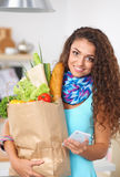 Smiling woman with mobile phone holding shopping bag in kitchen Royalty Free Stock Photos