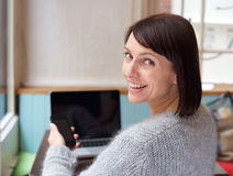 Smiling woman with mobile phone and laptop at home. Behind portrait smiling woman with mobile phone and laptop at home Stock Photos