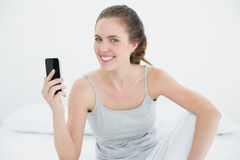 Smiling woman with mobile phone sitting in bed Royalty Free Stock Photos