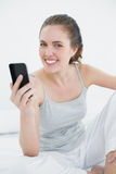 Smiling woman with mobile phone sitting in bed Royalty Free Stock Images