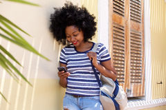 Smiling woman with mobile phone standing outside Stock Photography