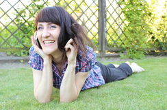 Smiling woman with mobile phone in sunny garden Royalty Free Stock Photos