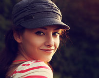 Smiling woman in modern cap looking outdoors Stock Images