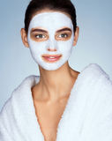 Smiling woman with moisturizing facial mask. Stock Photo