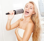 Smiling woman in the morning at bathroom. Woman in the morning at bathroom. Funny female sing song in comb Stock Photo
