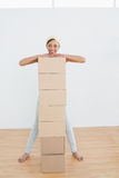 Smiling woman moving in new house with a stack of boxes Royalty Free Stock Photos