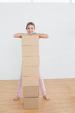 Smiling woman moving in a new house with a stack of boxes Stock Photo