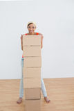 Smiling woman moving in a new house with a stack of boxes Royalty Free Stock Photo