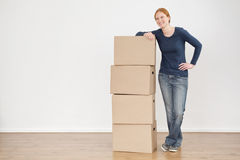 Smiling Woman with Moving or Storage Boxes. Full length photo of a young woman standing next to a stack of storage or moving boxes and smiling Royalty Free Stock Images