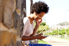 Smiling woman with mp3 player sitting in park Royalty Free Stock Image