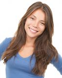 Smiling woman - Multiracial. Multiracial woman smiling looking at camera wearing blue blause. Mixed chinese / caucasian female model isolated on white background Royalty Free Stock Photography